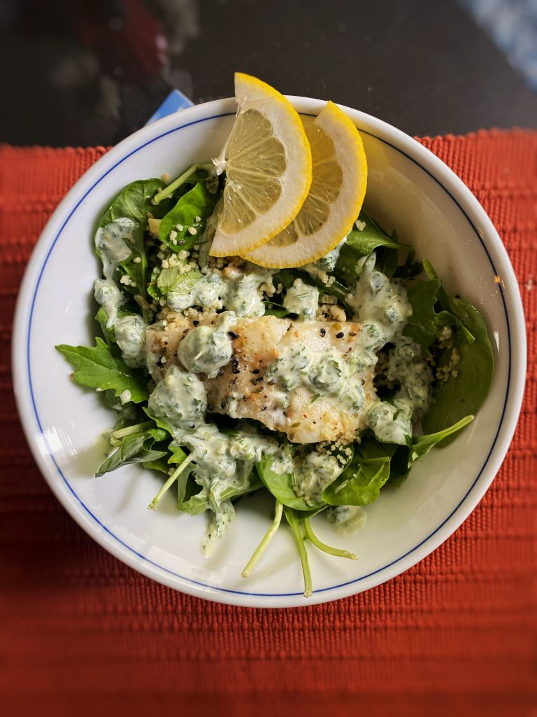 lemon parsley pacific cod with greens and lemon wedges