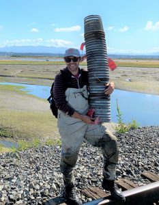 A researcher in chest waders and sun glasses stands with a tall stack of minnow traps rested on his hip, and smiles in front of a channel at Padilla Bay.